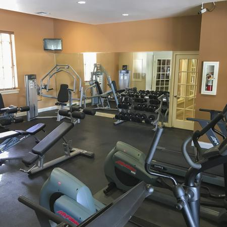 Community fitness center with various exercise equipment and wall mounted television.