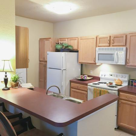 Kitchen with two seat breakfast bar, wooden cabinets, white appliances.