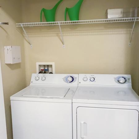 Open closet showing side by side washer and dryer, shelf.