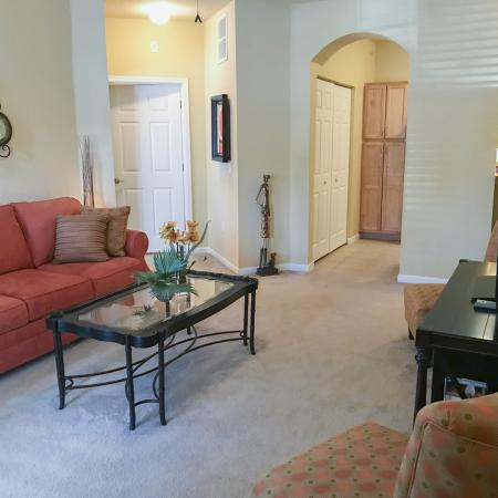 Carpeted living area with cloth covered red couch, glass coffee table, entertainment stand, and doorways into kitchen and bedroom.