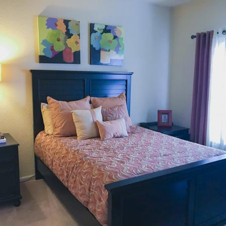 Carpeted bedroom with dark wood bed, night stand with lamp and clock on top.