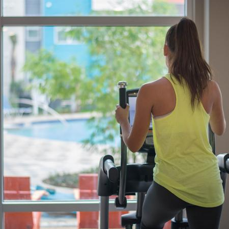 Young woman working out on step machine, looking out window to the pool.