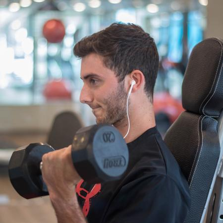 Young man lifting weights and listening to earphones.
