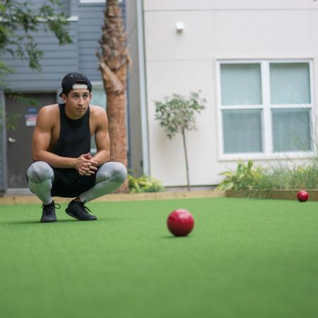 Young man playing boccie ball with building in background.