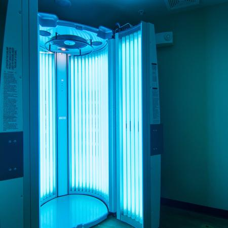 Community tanning booth, turned on.  Blue light emitting from the open doors.