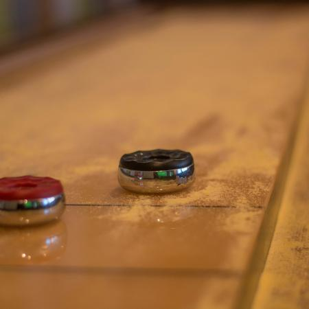 Close up of shuffleboard table with two shuffleboard pieces and sand on table.