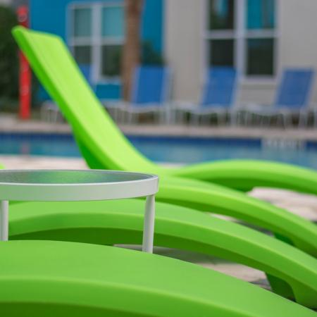 Close up of green lounge chairs with the pool in background.