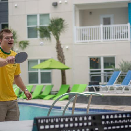 Young man playing table tennis along side the community pool.