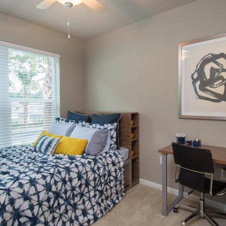 Another bedroom with blue and white bedspread.  Desk and chair on the right.  Large window with open horizontal blinds.