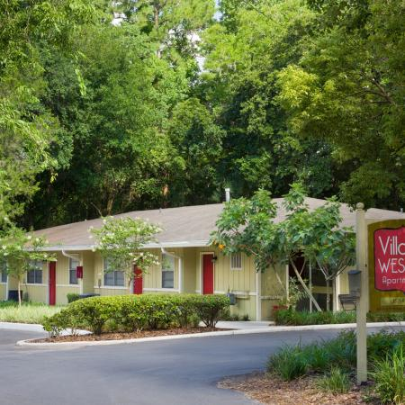 Village West monument sign with one level apartment building surrounded by a canopy of trees.