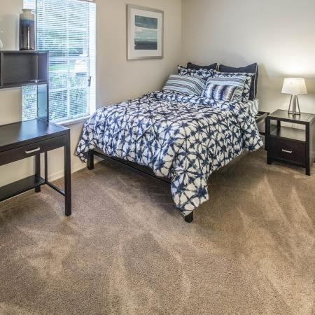 Carpeted bedroom with made bed, dark stained wood desk, tall dresser, nightstand with lamp.