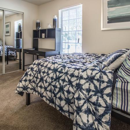 Carpeted bedroom with made bed, desk, closet with sliding mirrored doors, and window with open horizontal blinds.