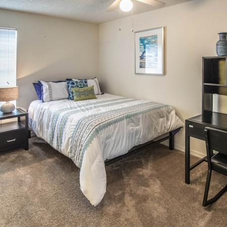 Carpeted bedroom with made bed, dark wood stained desk dresser and night stand with light.