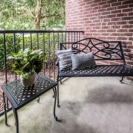 Cement floor patio with metal, outdoor chair with pillows and small end table.  Brick wall in background.  Patio is enclosed by a black railing.  Lush landscaping in background.