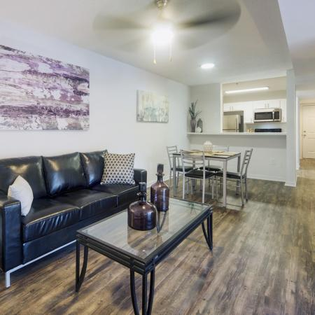 Living and dining area with wood style flooring, modern leather couch, glass coffee and end tables, and a square dining room table with four chairs in the background.