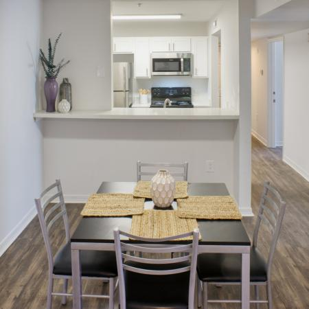 Dining area with wood styled flooring, small square table with four chairs and four place settings.  Kitchen in background.