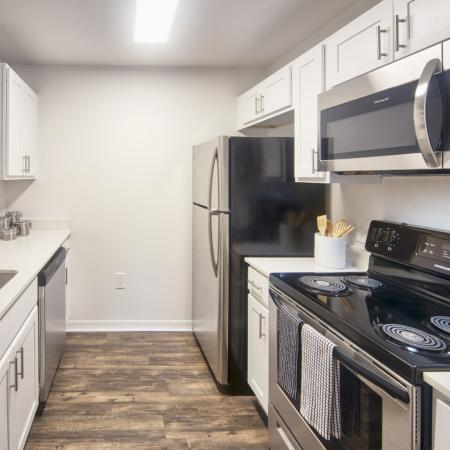 Galley style kitchen with wood style flooring, black appliances,white cabinets and single tub sink.