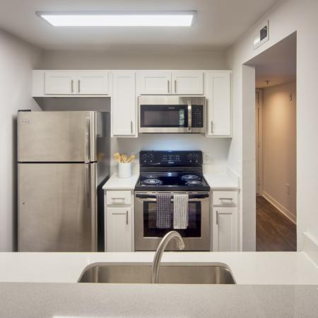Kitchen with white cabinets, stainless steel appliances, single tub sink.