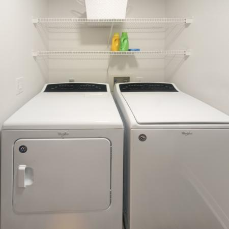 Side by side washer and dryer with two shelves above.