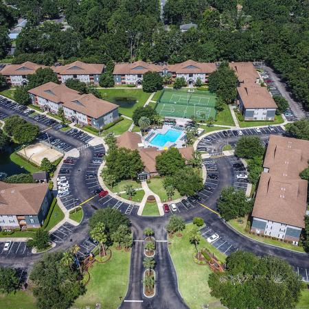 Overhead shot of the entire Lexington Crossing property, taken from a drone.  Buildings, grass, trees, pool and tennis courts are visible.