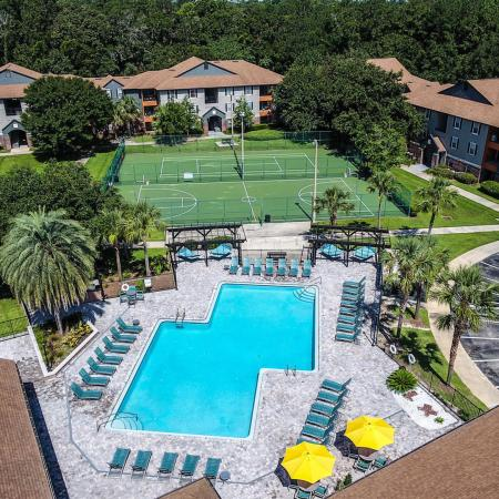 Overhead photo of community pool lined with lounge chairs, palm trees.  Tennis court, basketball court, and apartment buildings in the background.