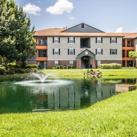 Lexington Crossing pond with fountain and grassy area, building exterior