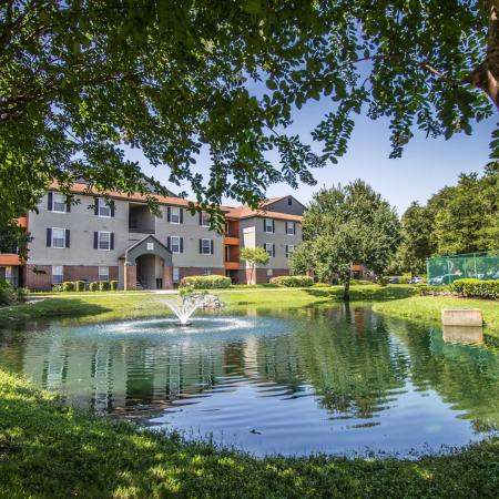 Lexington Crossing Pond with fountain through arching trees, building exterior.