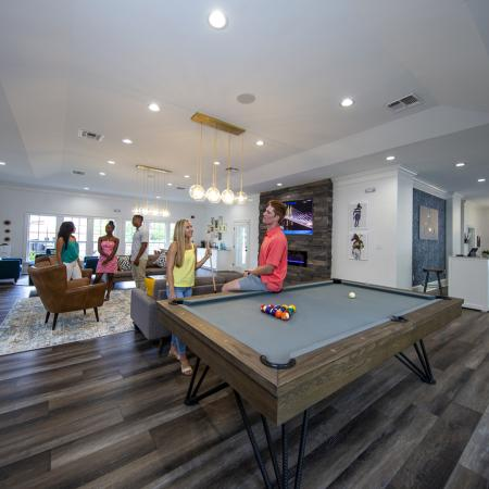 Community clubhouse with pool table in foreground, and young people talking in movie viewing area in background.
