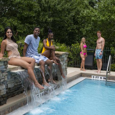 Five young people posing around the community pool.  Three of them are sitting on top of stone waterfall.