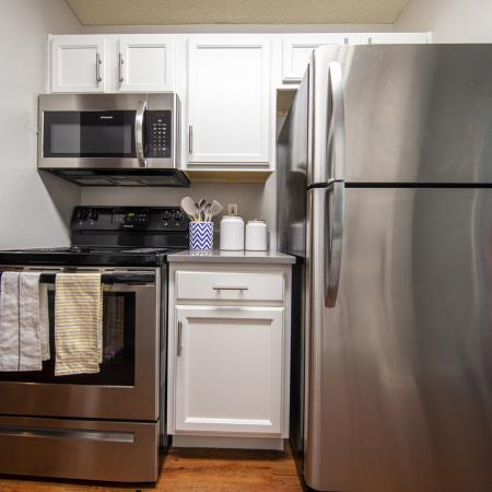Stainless steel oven, microwave, and refrigerator, white cabinets and wood style flooring.