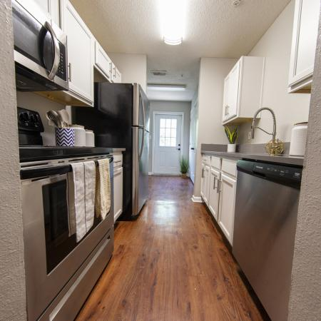 Galley style kitchen with wood flooring, stainless steel appliances, white cabinets.
