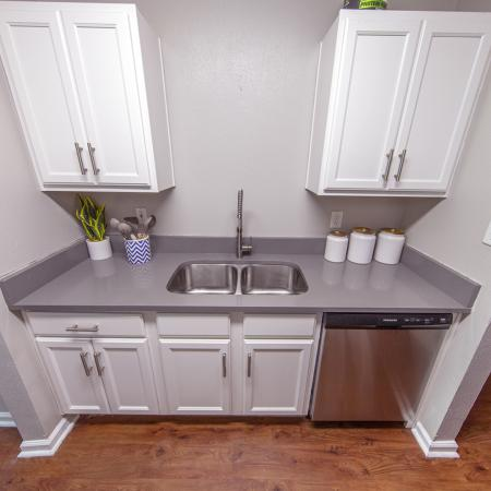 One side of galley kitchen that includes double sink, white cabinets, and stainless steel dishwasher.