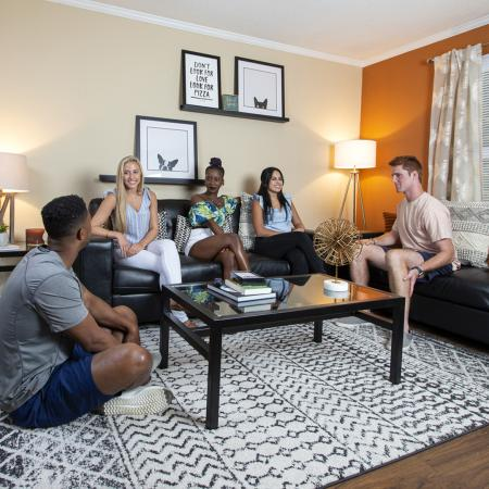 Group of young adults talking around a glass coffee table in a living room.