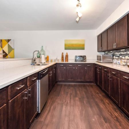 Galley style kitchen with wood style flooring, wood cabinets, stainless steel appliances.