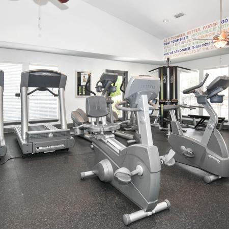 Fitness center with treadmills, cardio bikes, and other various pieces of workout equipment.