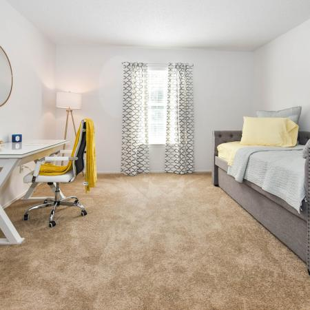 Carpeted bedroom with day bed with pillows on right, desk and chair on the left.