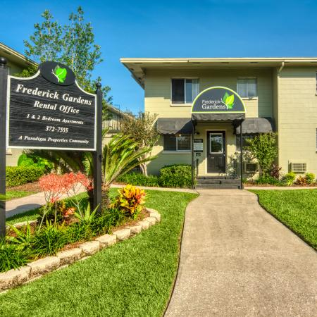 Community Leasing Office with sidewalk leading up to it and surrounded by green space.