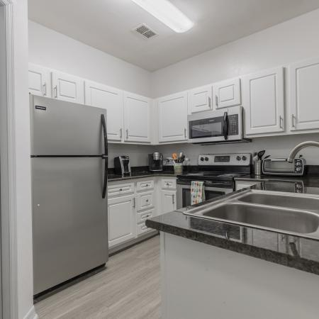 Kitchen with hardwood floors, white cabinets, black granite style countertops, and stainless steel appliances.