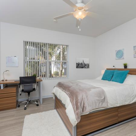 Bedroom with hardwood floors, area rug, study desk with chair, bed, end table with a lamp, and a window.