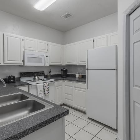 Kitchen with white tile floor, white appliances, white cabinets, and black countertops.
