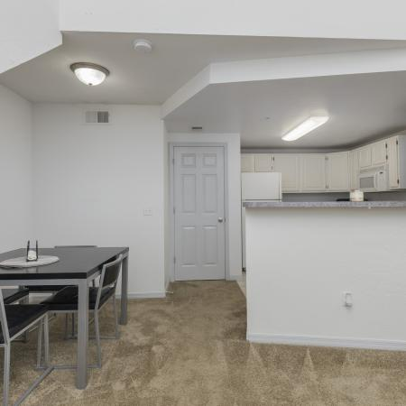 Carpeted living space with square dining set, white wall, and passthrough looking into the kitchen.