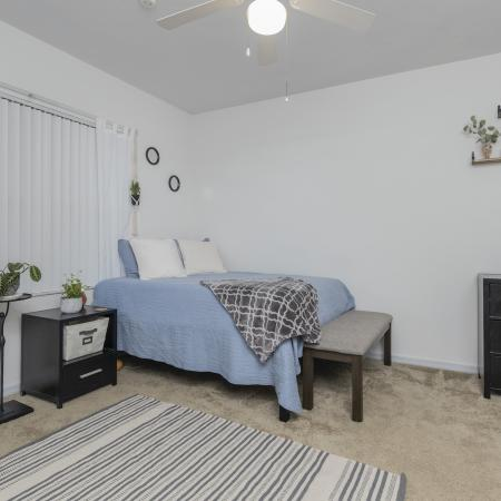 Carpeted bedroom with white walls, a large window, end table, drawer, area rug and ceiling fan.