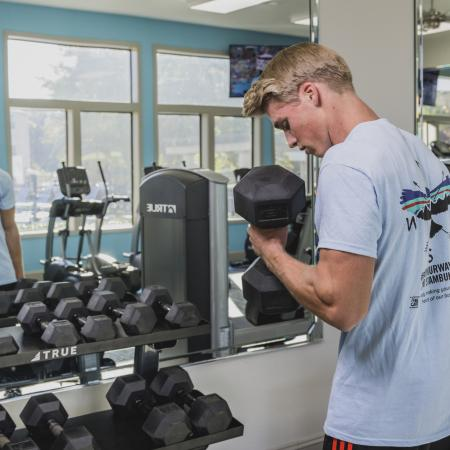 A young adult male wearing a blue shirt is lifting weights at the community gym.