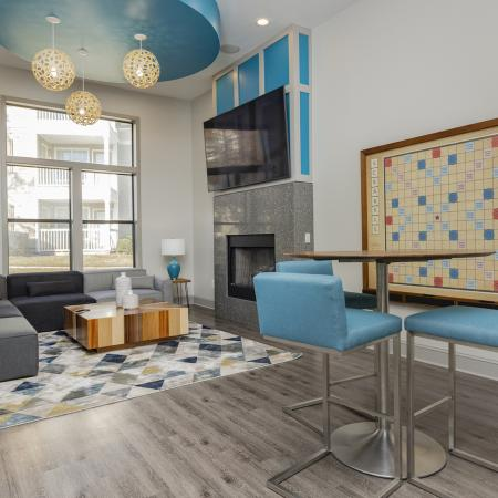 Community clubhouse area with a wall mounted TV, large windows, area rug, bar height dining set, fireplace, and a large couch.