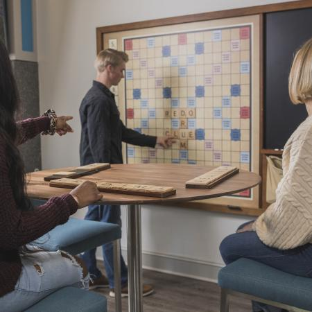Two young adult females point at a young adult male who is playing giant sized scrabble mounted onto a wall.