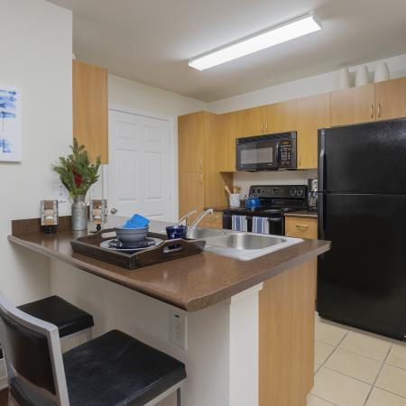 Kitchen with tile floor, passthrough, black appliances, and brown countertops.