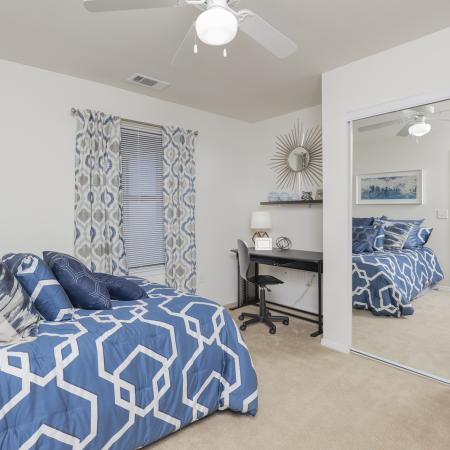 Carpeted bedroom with mirrors, closet, bed, desk. window, and ceiling fan.