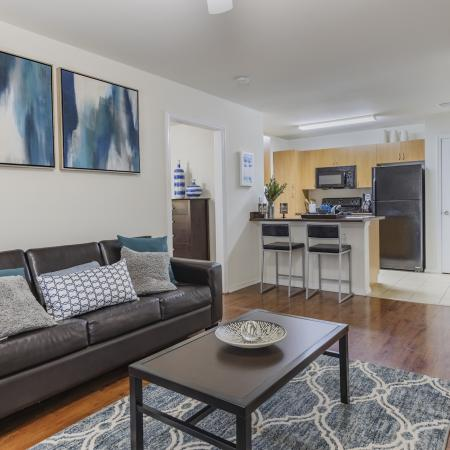 Living room with hardwood floors, kitchen passthrough, leather style couches, wall art, and access to private bedrooms.