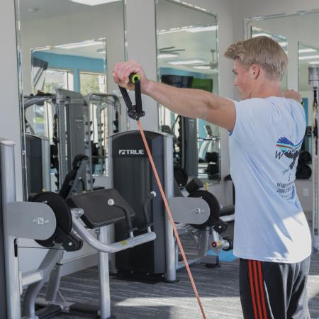 A young adult male wearing a blue shirt using resistance bands at the community gym.