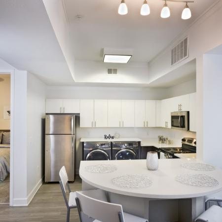Lux 13 Apartments interior: kitchen, dining room table, washer/dryer, fridge, microwave  and oven